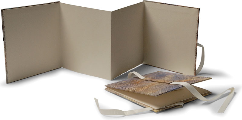 Mantle books with paste paper covers are intended for use with photos or small memorabilia, to sit open on a flat surface.