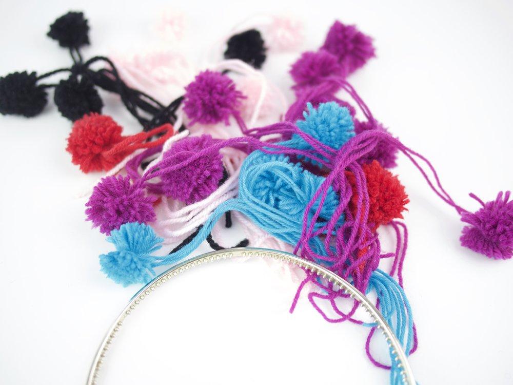 - Nehmt den Haarreifen. Am besten ihr habt einen mit diesen Kämmen. Dadurch halten die Pompons noch besser und verrutschen nicht.Knotet sie einfach um den Haarreif drumherum.