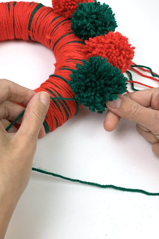 13. - Wickle die Pompons um den Kranz herum und mache einen festen Knoten.
