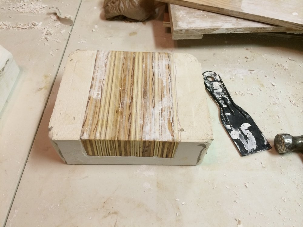 Even with angled positives and oil soap, we couldn't get the wooden tiles out of the plaster, so we started over and cast the plaster so that two ends of the wood positives were exposed.