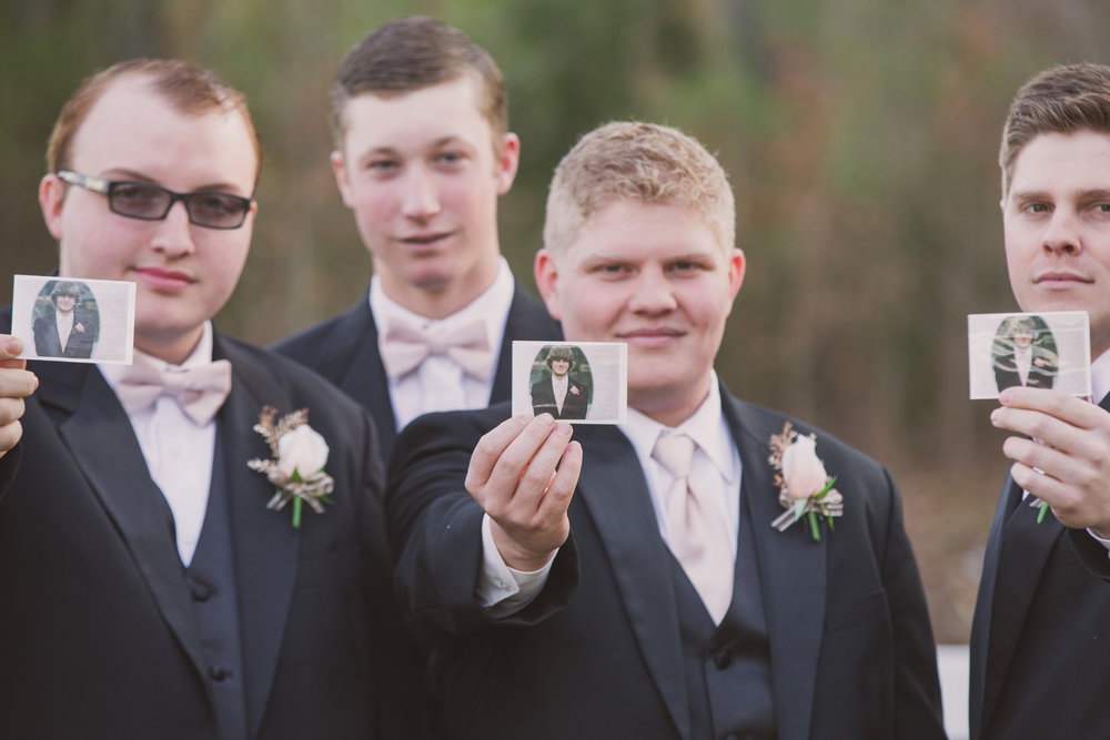 His childhood best friend had passed away. He wanted to have him there on his wedding day so he copied his picture for his groomsmen to carry for him to be there in thought and memory.