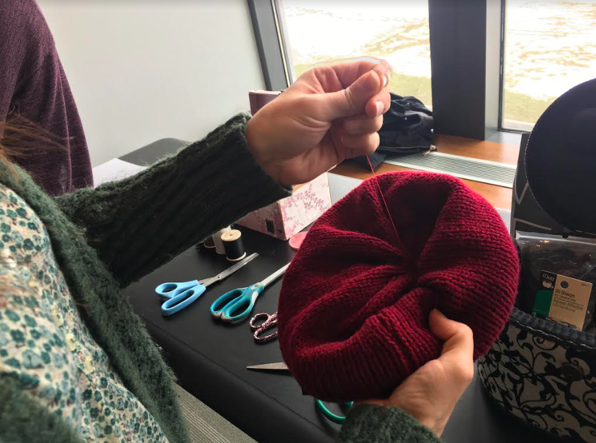 A workshop volunteer repairing Katherine Maradiaga's hat.