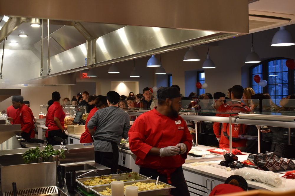 Hundreds of students fill the new dining center, eager to try free food samples from the various stations.