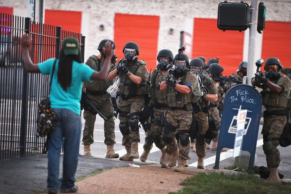 Police, fully loaded, point guns at an unarmed man in Ferguson, Missouri. Photo Source: http://vox.com