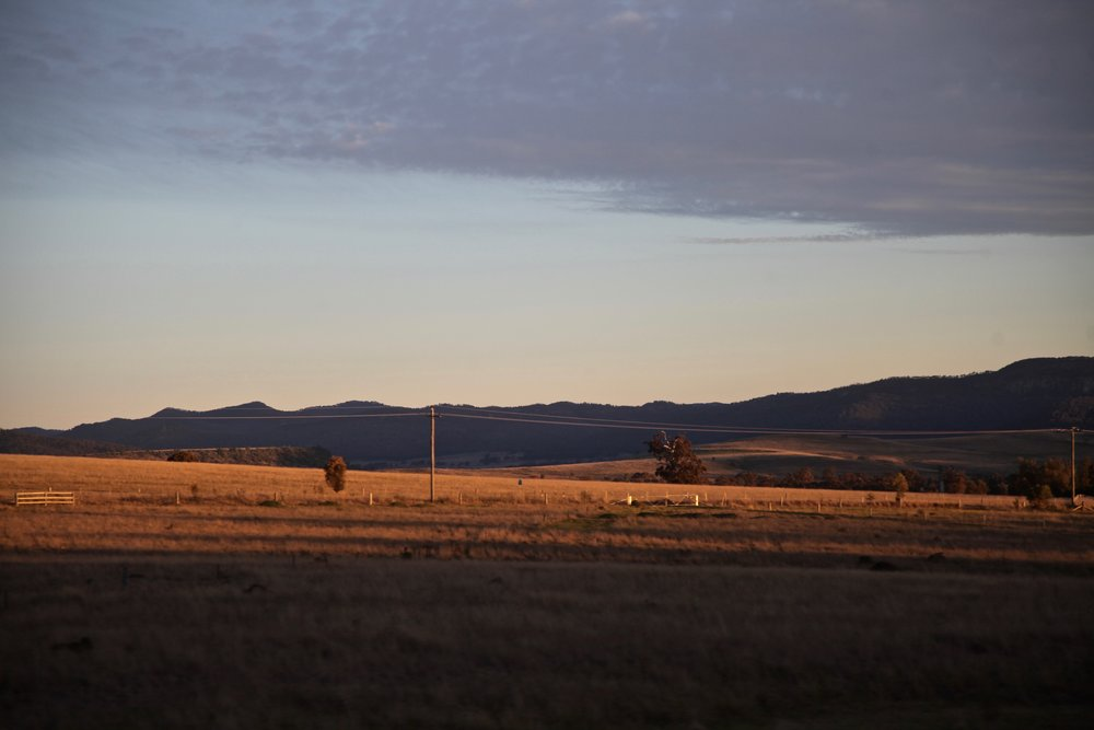 The sun sets over farmland in the Hunter Valley, NSW.