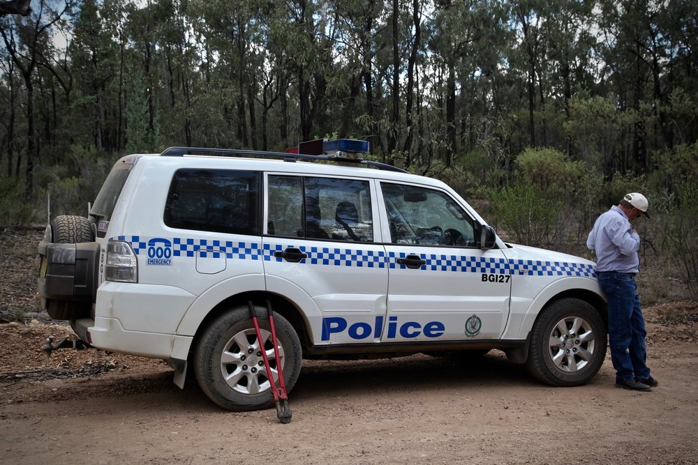 A coal mine manager leans on a police car, alongside bolt cutters, at the site of a protest against coal mining in Leard State Forest. December 2013.