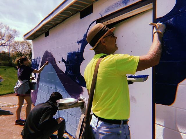 Mark and friends painting the background of a mural at Mural Fest