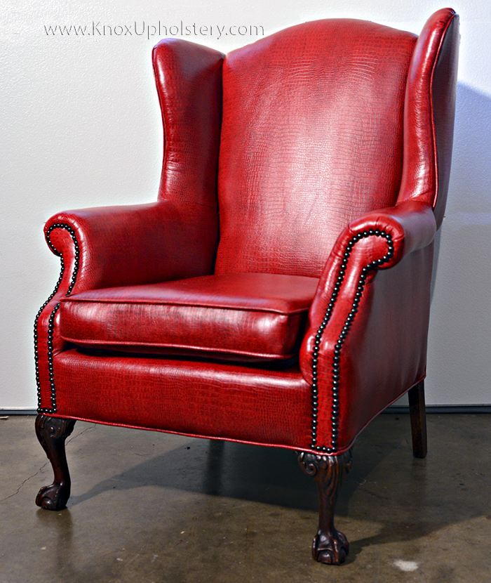 Red upholstered wingback chair with nailhead trim.jpg