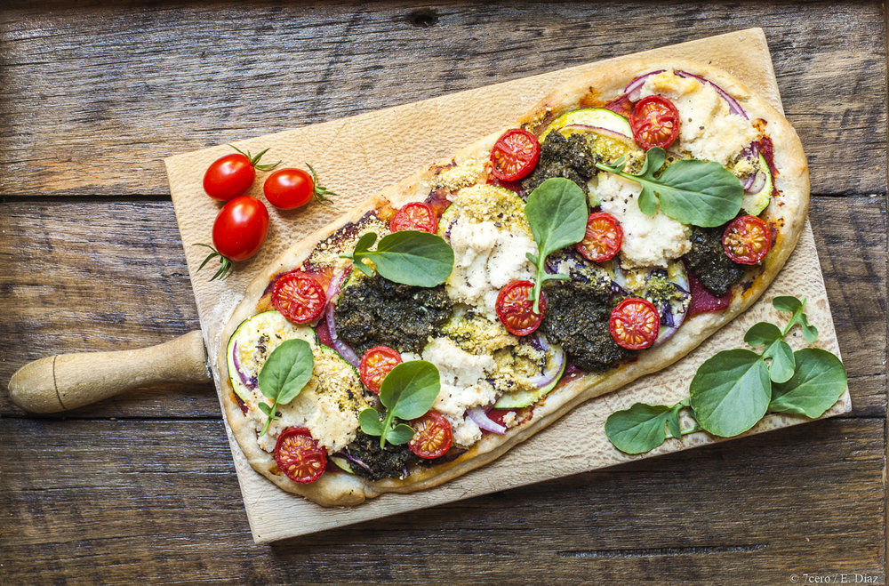 Almond ricotta and vegan parmesan on a zucchini, cherry tomato and pesto pizza, perfection!