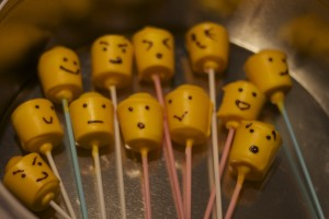 marshmallows covered in yellow candy melts decorated to look like lego faces
