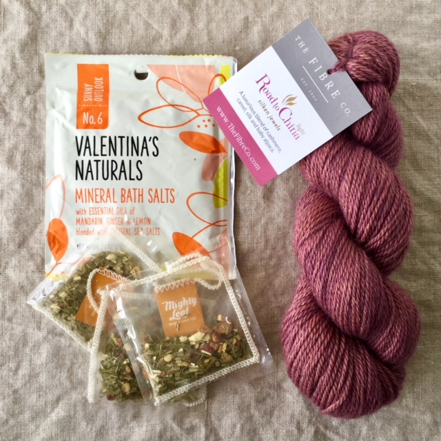 A skein of the Fibre Co.  Road to China Light  in the Carnelian colorway, Mighty Leaf Ginger Twist Tea, and Valentina's Naturals Sunny Outlook Mineral Bath Salts