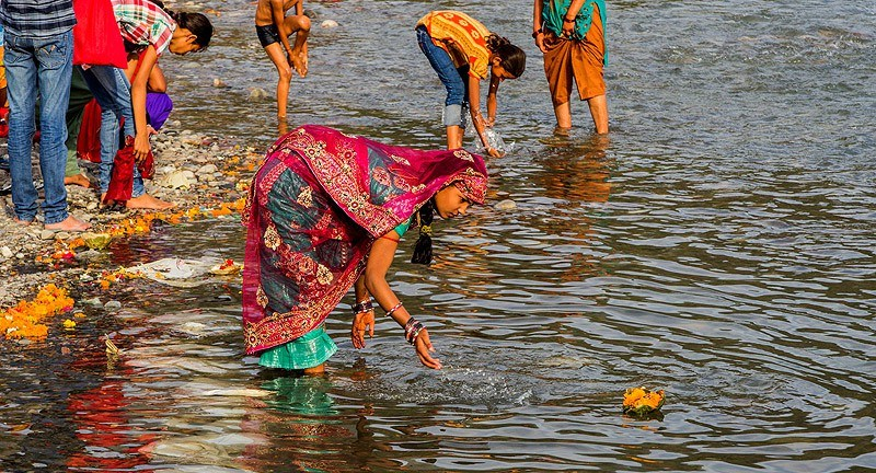 16382983986-young-indian-woman-making-an-offering-ganges-river-triveni-ghat-india-e1458058030225.jpg