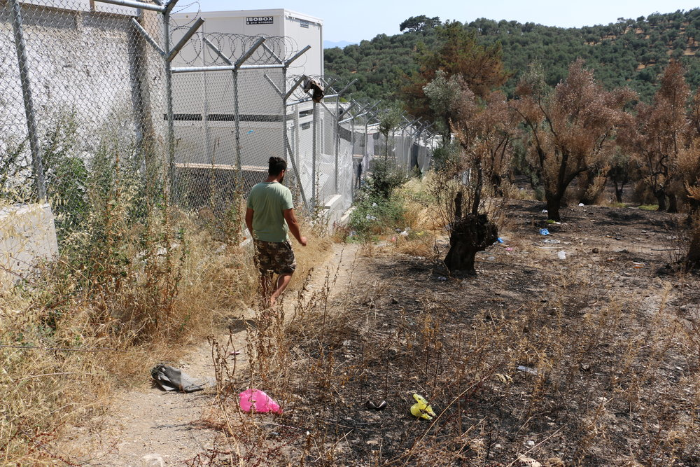 Omar checks the perimeter of Moria Camp after a fire in an olive grove outside the fence in June 2017.