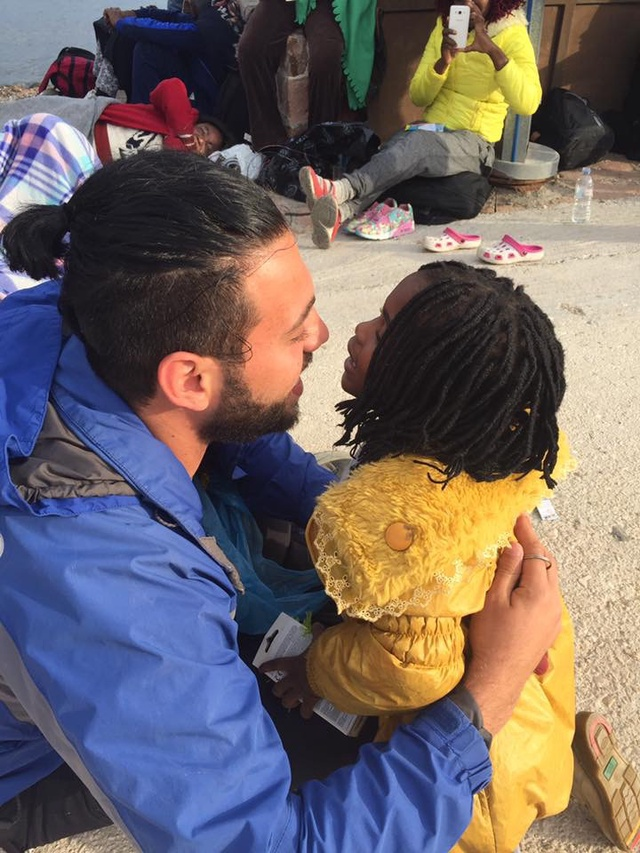 Omar comforts a young girl who had recently landed by boat on Lesvos.