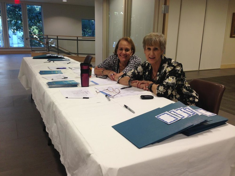 Mary Helen Casseday and Jerri Doctor sit with smiles and check attendees in as they arrive.