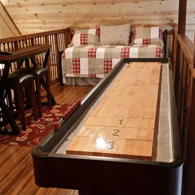 The loft at Time Well Wasted!  Shuffleboard! 2 daybeds and a smart TV..Perfect for the kids. Book now at www.brokenbowlakewoodluxurycabins.com