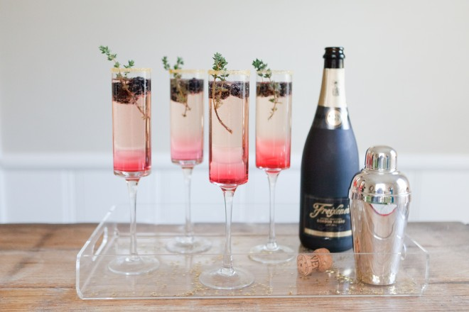Blackberry Champagne Cocktail - Ingredients1 c. blackberries + 8 more for garnish1 c. Water1 c. sugar1 bottle of champagne4 ounces or 1/2 c. gin1 c. iceInstructionsIn a small saucepan, bring blackberries, water, and sugar to a boil. Reduce heat and simmer for 10 minutes, until the blackberries are soft and the simple syrup has turned to a bright pink/redish color.Remove from heat, drain blackberries, and allow to cool. This step can be done well in advance as the syrup will keep for at least a week in the refrigerator.Prepare your champagne glasses.Next, begin by adding 1 ounce of gin to each champagne glass.Next drop two blackberries in each glass, followed by 2 ounces of homemade blackberry simple syrup.Fill the rest of the glass with champagne.