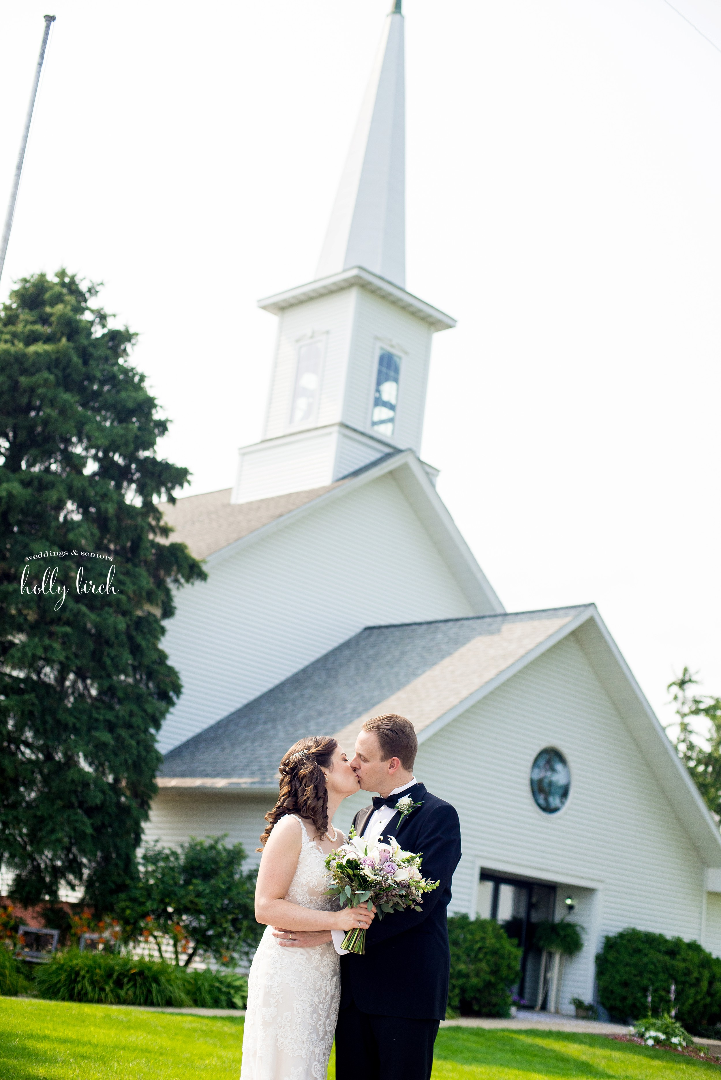 bride and groom with white country church