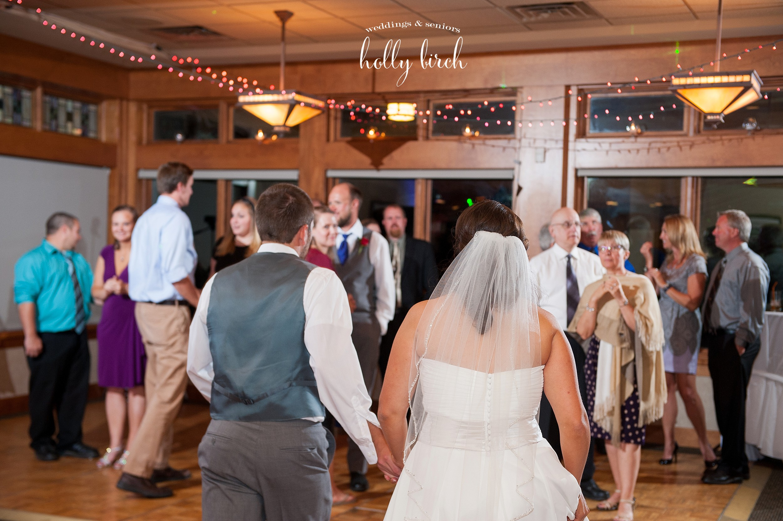 bride and groom join their guests on dance floor