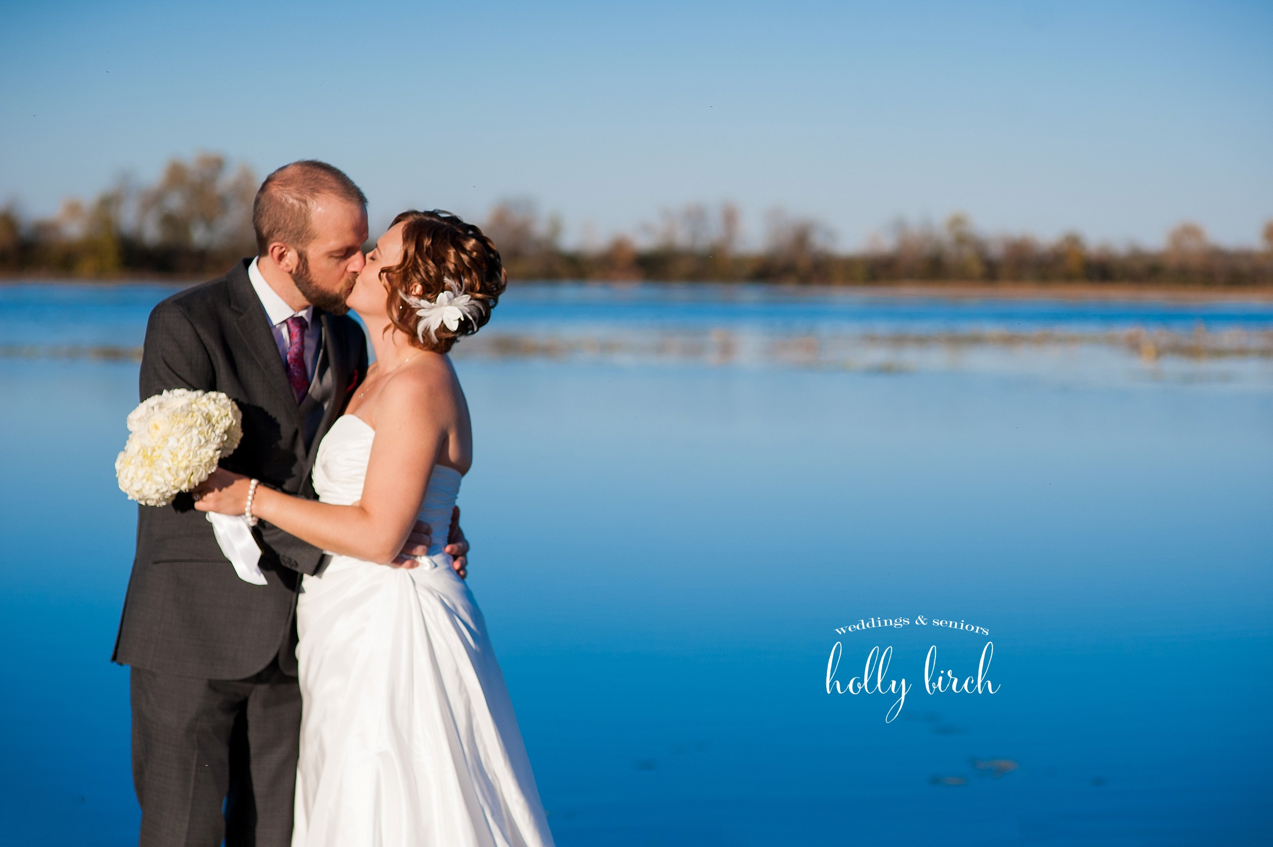 bride and groom with still blue lake water