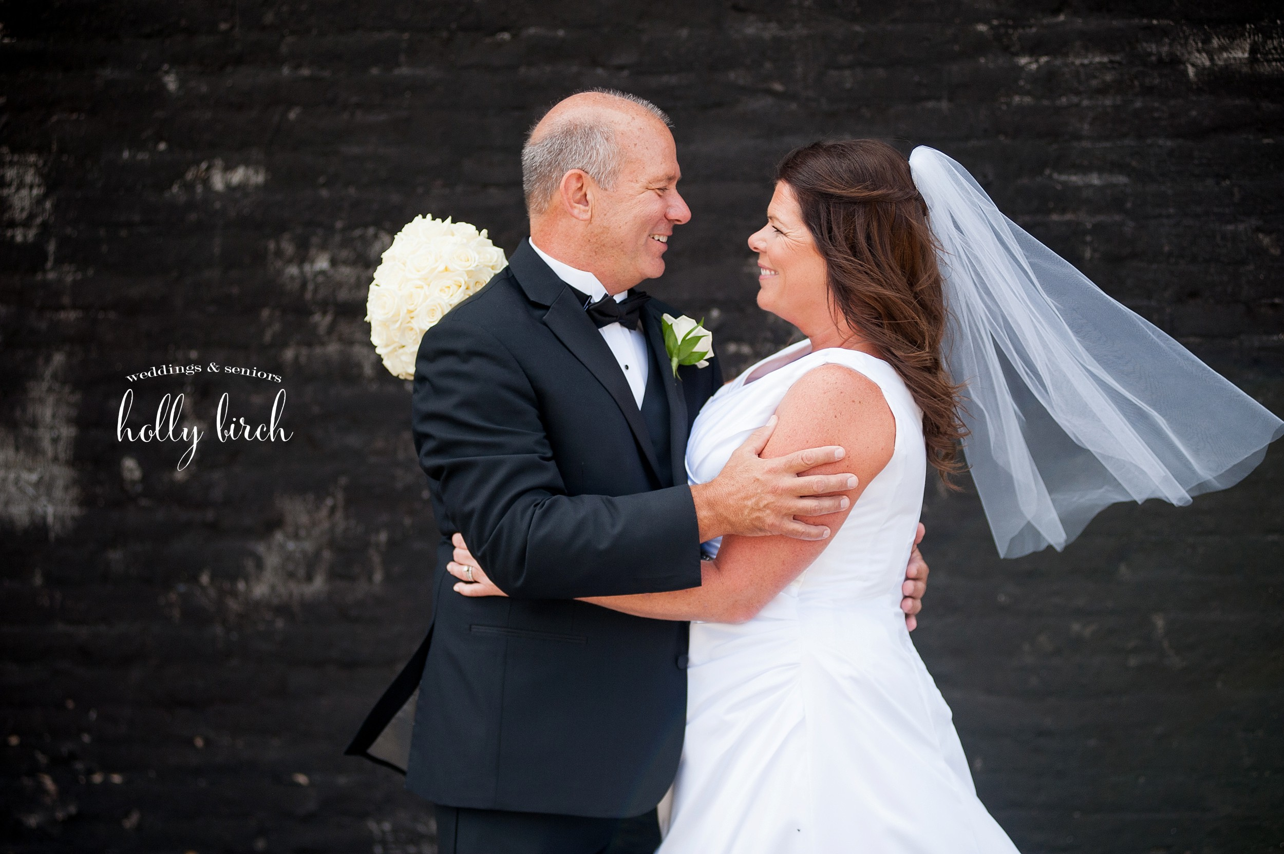 bride and groom with black brick wall