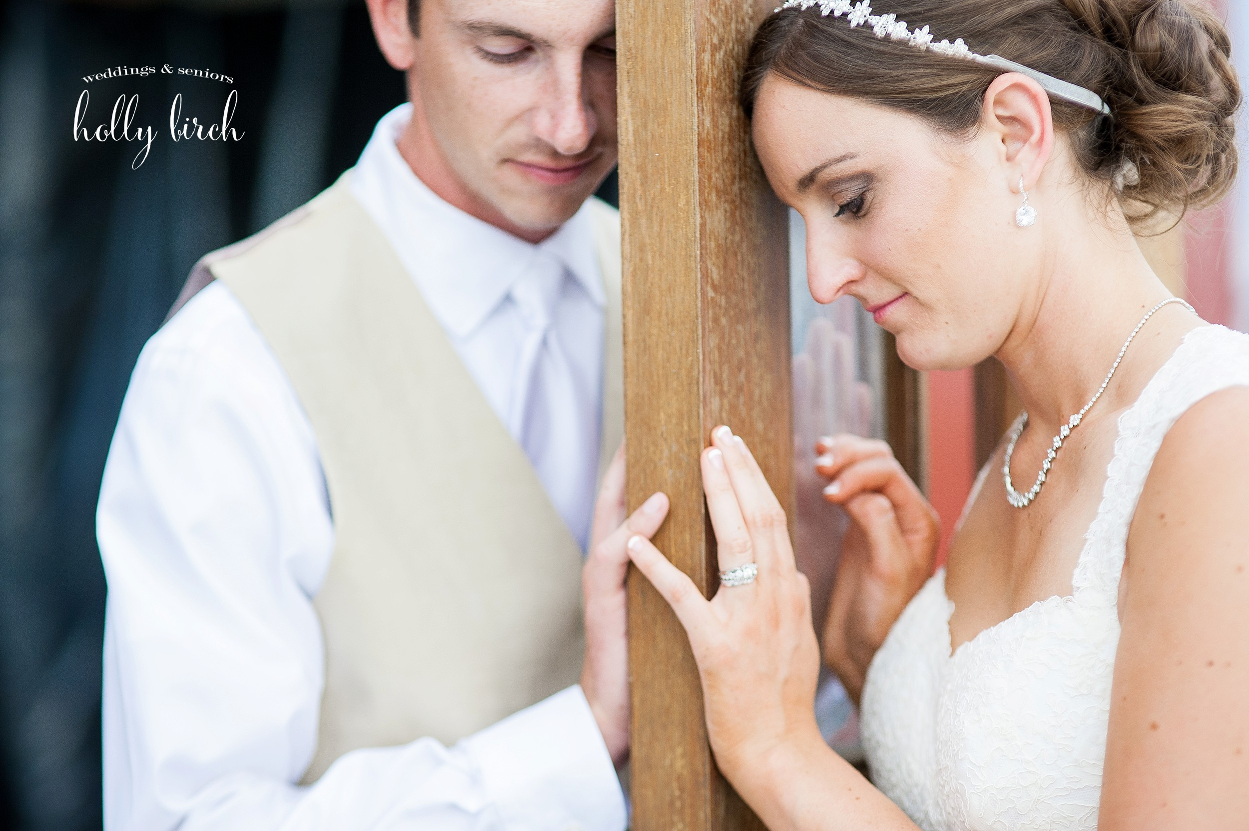 bride and groom on either side of wooden door