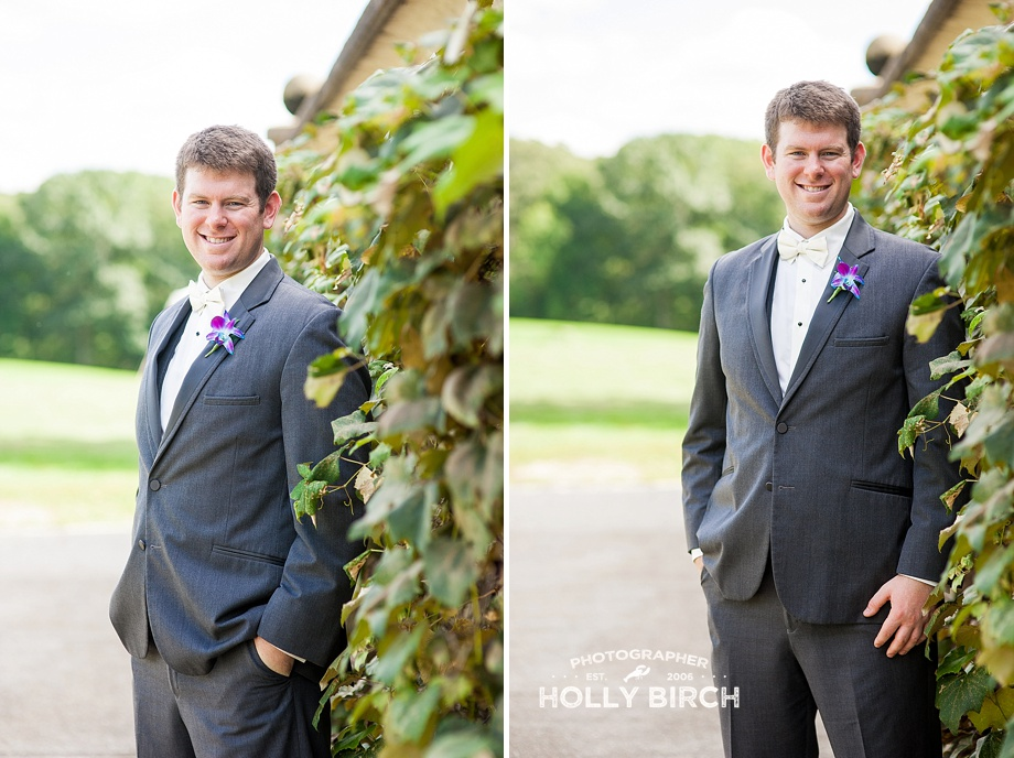groom in gray tux with grapevine wall