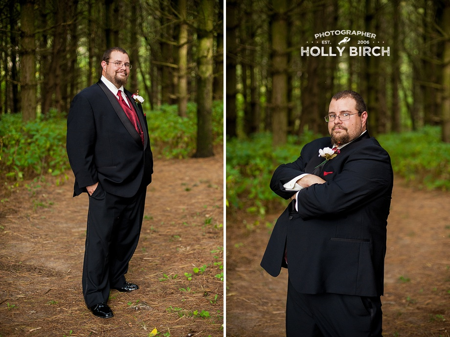 groom poses in forest