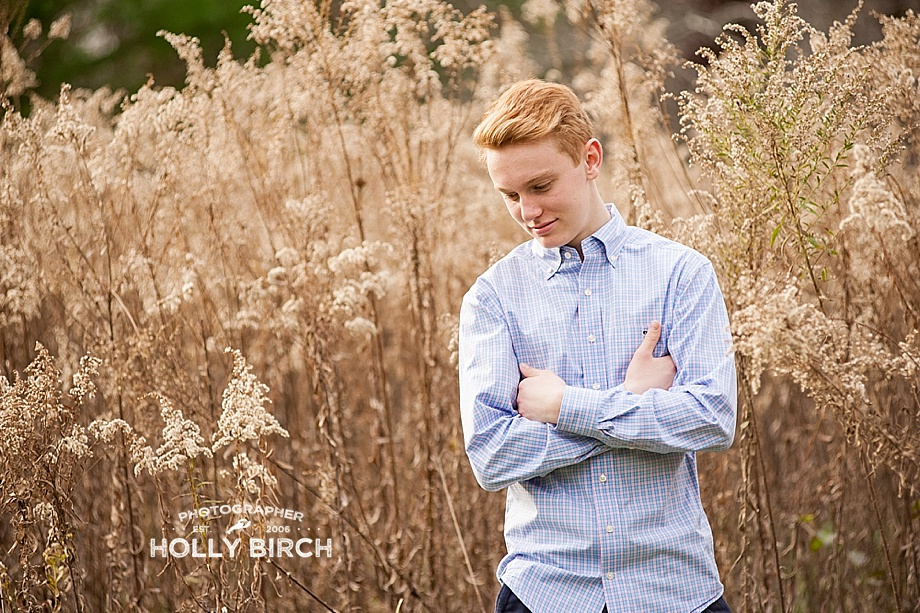 senior guy in blue button up with tall grass