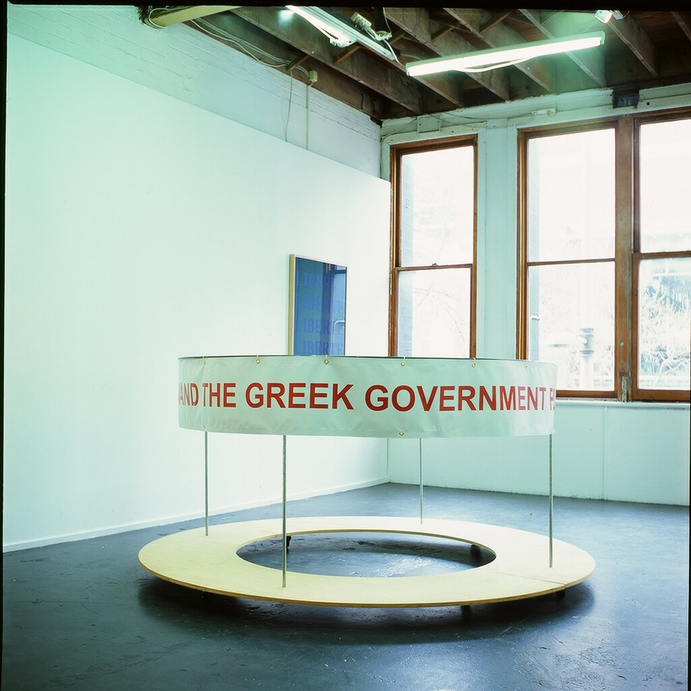 Portable Protest Pod, 2016, We demand the Greek Government find a Solution for Syrians in Greece ( Quote from the streets of Athens, June 2016 ) Plywood, Metal rod, Castor Wheels, Vinyl , 240 cm diameter x 100 cm