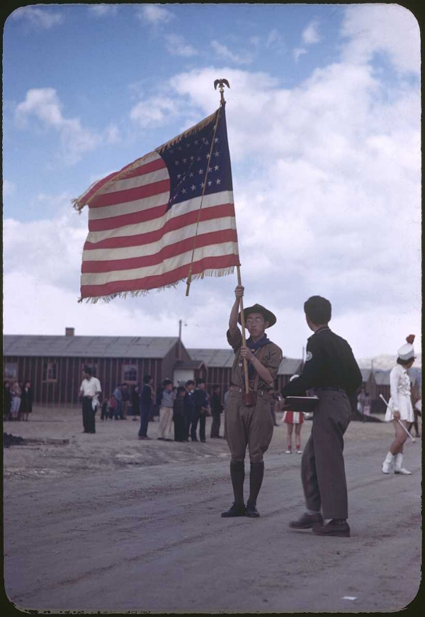Heart Mountain Relocation Center, Heart Mountain, Wyoming, 1943. A boy scout carries the flag at a parade. Kodachrome slide shot by Bill Manbo, a prisoner.  (c) Takao Bill Manbo