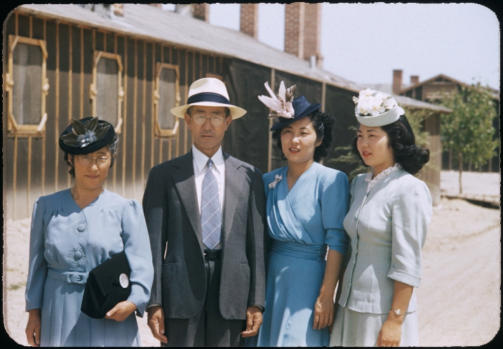 Mary Manbo (second from right) stands in front of a Heart Mountain barrack with her parents, Riyo and Junzo Itaya (far left and second from left respectively) and her younger sister Eunice Itaya.  Her husband Bill took the photograph, using Kodachrome slide film, a technology that was in its infancy in 1943.    Photo (c) Takao Bill Manbo.