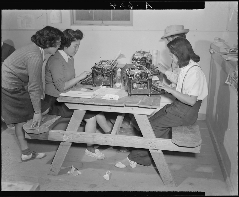 Tule Lake Relocation Center, Newell, California, November 2, 1942.  Writers and editors work at the city desk of the Tulean Dispatch, the camp's newspaper.