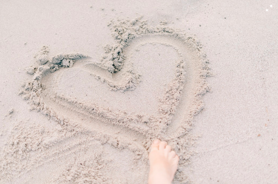 heart drawn in the sand with right foot