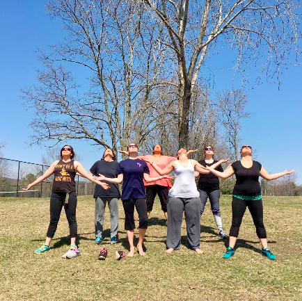 Women from Hanson House practicing movement exercises outdoors