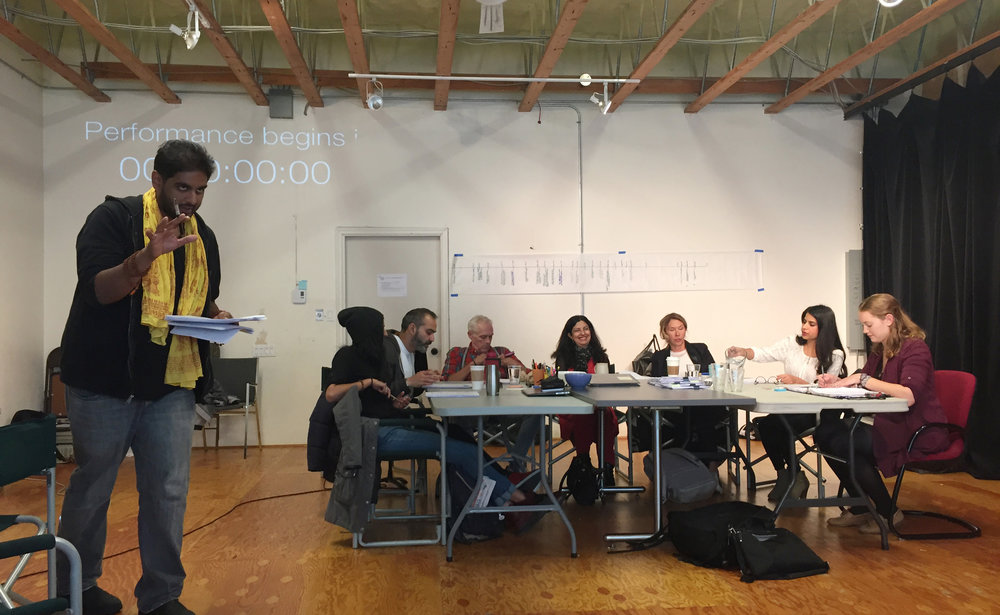 (L to R: Director Jiv Parasram speaks to audience at workshop reading of  Victim Impact . Outreach Coordinator Gavan Cheema, performers Munish Sharma, Allan Morgan, Nimet Kanji, Jenn Griffin and Risha Nanda, and stage manager Heidi Quicke. Photo: Belinda Bruce)