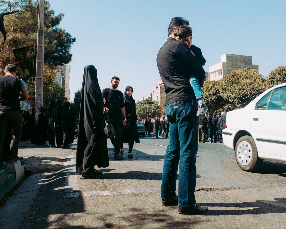 A family watching an Ashura procession - Hengam Street, Tehran