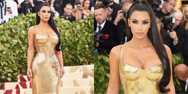 Kim Kardashian in een jurk van atelier Versace. Haar haren voor de helft opgestoken in een strakke hoge staart.