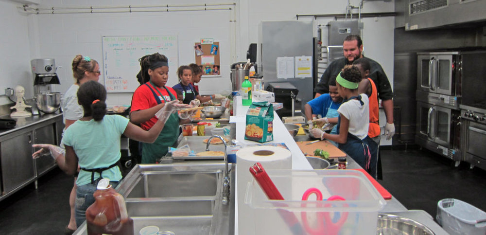 Inside Out's Community Kitchen is crowded with eight young chefs at work. Photo by: John Carlson