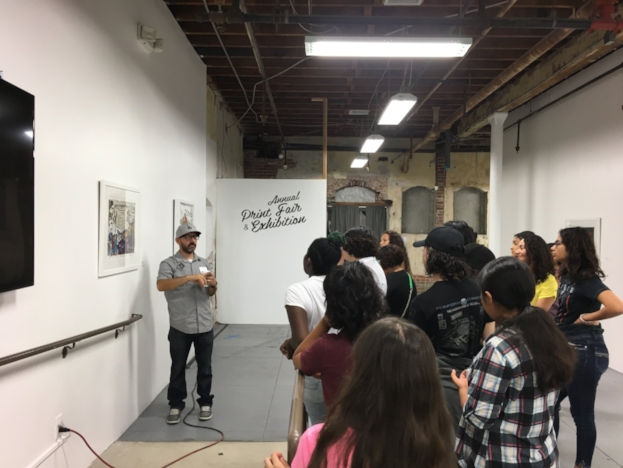 Arts Educator and Printmaker, Luis Genaro Garcia, leads a youth tour of the Print Fair Exhibition at SHG with SOY Artista students.