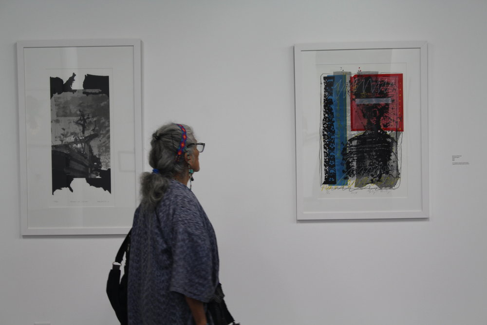 Master Dia de los Muertos Altar Maker and longtime SHG supporter, Ofelia Esparza, takes moment to view  Miranda Rights  at the 45th Annual Print Fair and Exhibition.