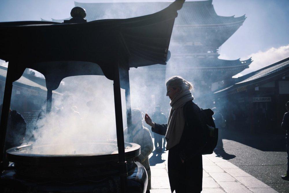 Wellesley Boboc wafting smoke at Asakusa Shrine in Tokyo, Japan. January 2017.