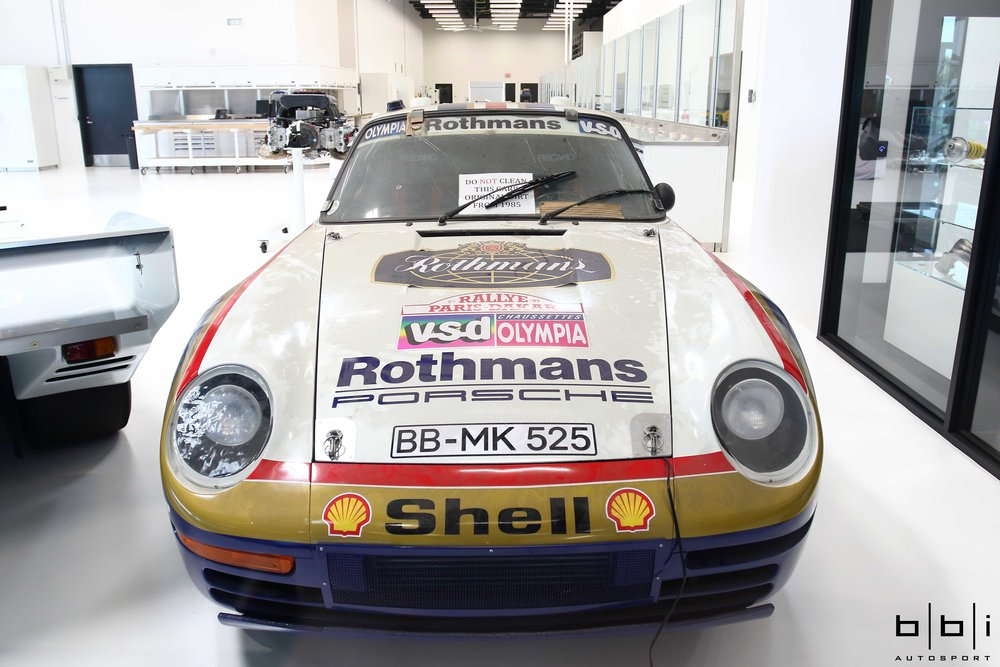 A glass wall in the entrance hall of the Porsche Experience Center gives visitors a glimpse into the workshop, where historical racing cars are repaired and track vehicles are maintained.