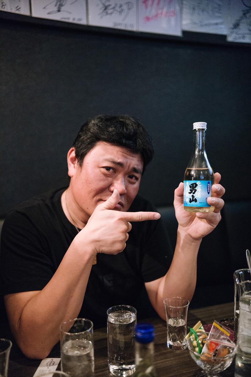 makoto takeishi and a bottle of sake.jpg