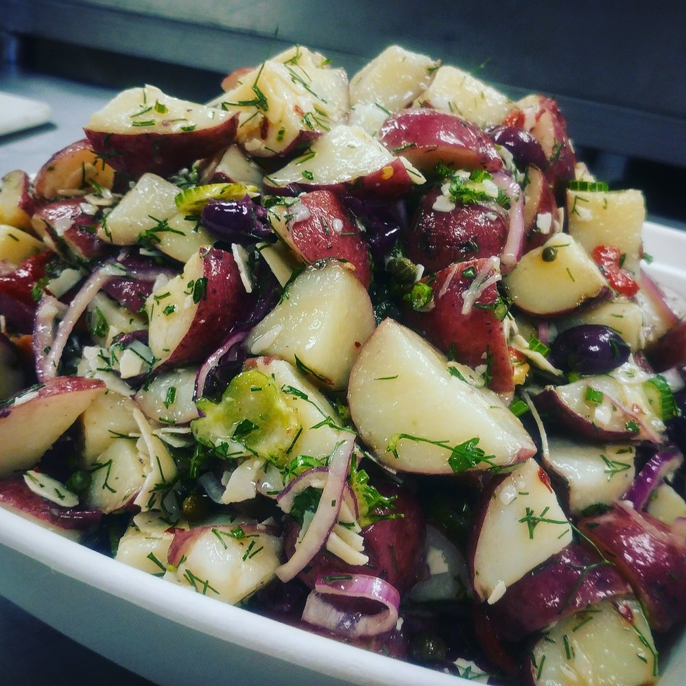 Mediterranean Potato Salad - Kalamata olives, shaved parmesan, red onion, capers, roasted red peppers, and fennel. Tossed in a white wine vinaigrette.