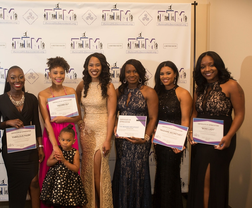 "The Troubled Movement's Board of Directors at the annual ""Marching Forward"" Fundraising Gala on March 4, 2017. Left to right: Falen Hardge, VP; Anamechia Joseph, Program Director; Maranda Evans, President; Nicki Ezeh, Honorary President; Sade' Alston, Secretary; Shariese Martin, Treasurer. OH! The little one is Zoe, our little precious mascot."