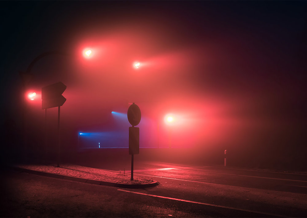 red traffic lights in the fog at night