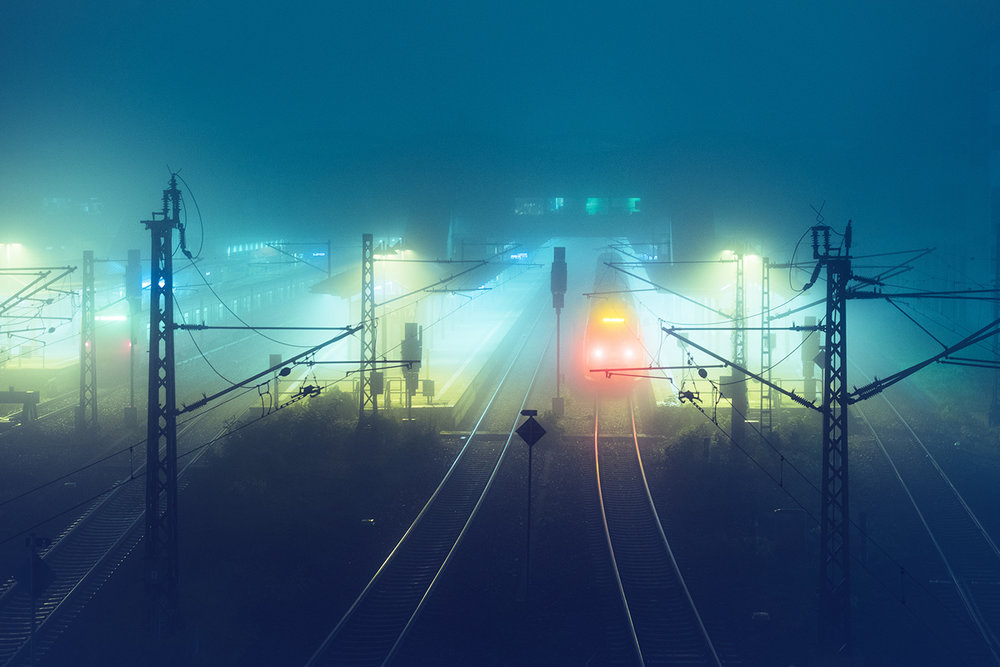train station at night with fog and blue, green, red lights