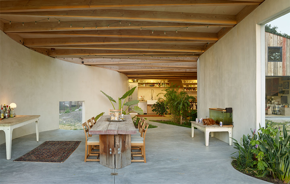 living room and dinner table of a tropical home with concrete walls by Mork Ulnes Architects