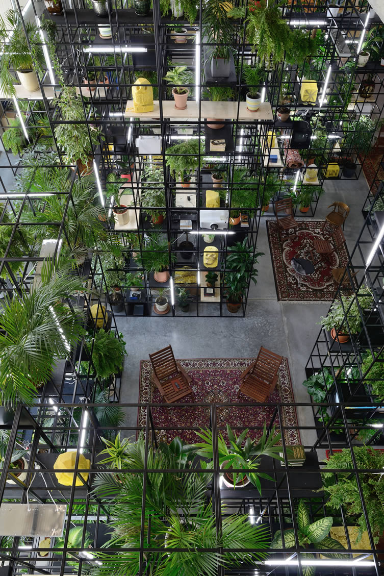 view from the top of Rashid Johnson's installation with carpets, seating, greenery and a black metal structure